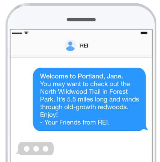 "text message reading ""Welcome to Portland, Jane. you may want to check out the North Wildwood Trail in Forest Park. It's 5.5 miles long and winds through old-growth redwoods. Enjoy! - Your friends from REI."""